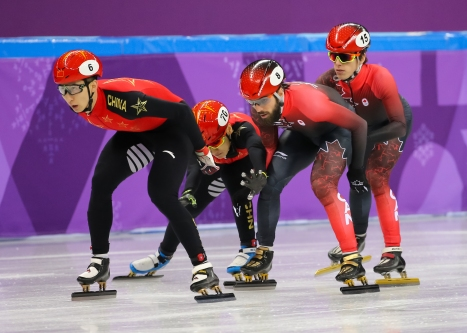 Charles Hamelin receiving a push from teammate Charle Cournoyer during the Men's 5,000m Relay heats. (Photo: Greg Kolz)