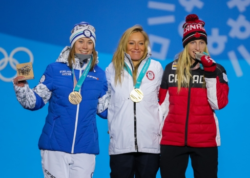 Laurie Blouin celebrates her Olympic silver medal in Ladies' Slopestyle alongside Enni Rukajarvi of Finland and Jamie Anderson of USA. (Photo: Greg Kolz)