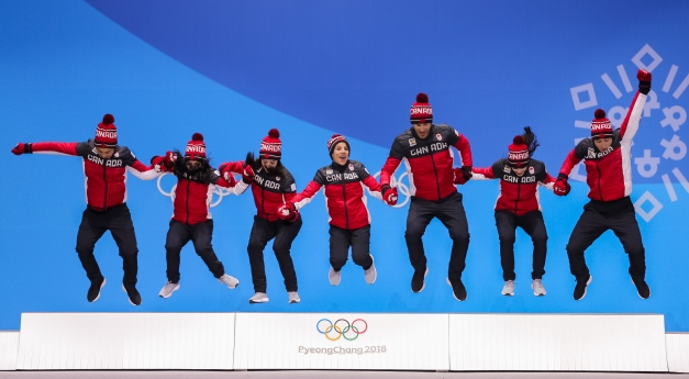 Canada's figure skaters jump atop the podium during the Team Event medal ceremony. (Photo: Greg Kolz)