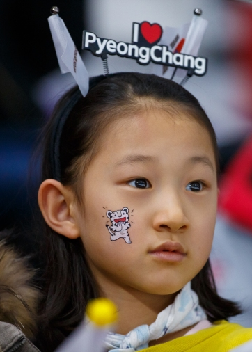 A young Korean fan watches intently as the Men's 5,000m event unfolds at the Gangneung Oval. (Photo: Greg Kolz)