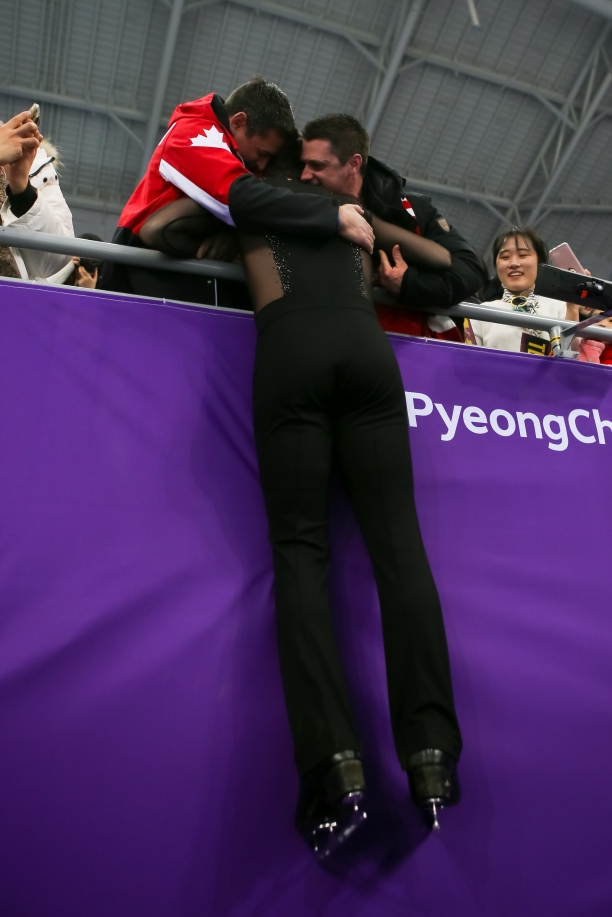 February 20, 2018: Scott Moir is embraced by his brothers following a gold medal performance alongside Tessa Virtue in the ice dance competition. (PHOTO: Greg Kolz)