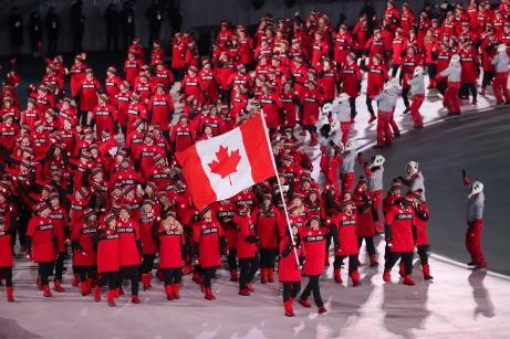 February 9, 2018: Flagbearers Tessa Virtue & Scott Moir lead Team Canada into PyeongChang Olympic Stadium during the Opening Ceremony. (PHOTO: Greg Kolz)