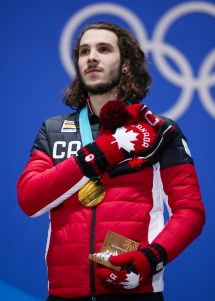 February 18, 2018: Short track speed skater Samuel Girard stands atop the podium during a medal ceremony celebrating his victory in the men's 1000m final. (PHOTO: Greg Kolz)