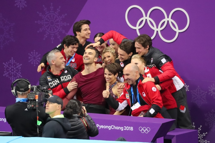 February 11, 2018: Pairs figure skaters Eric Radford & Meagan Duhamel are embraced by their teammates following their performance in the team competition. (PHOTO: Greg Kolz)